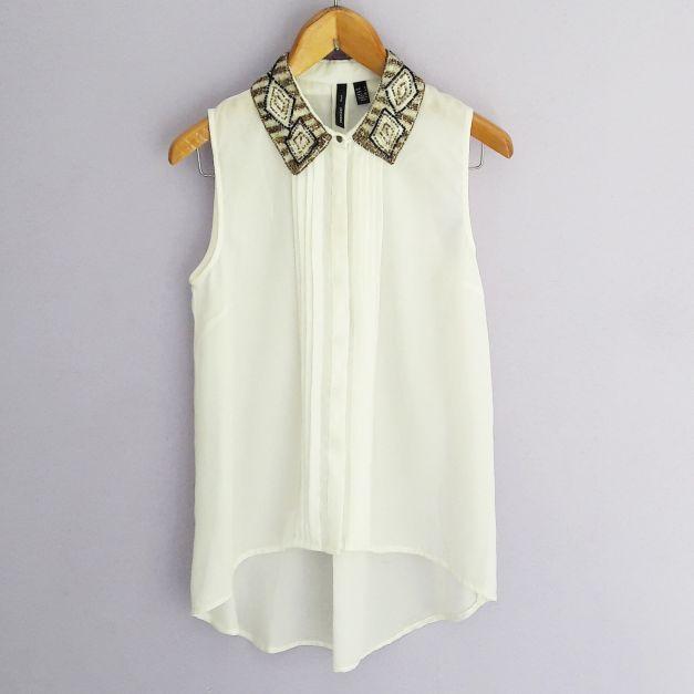 Blusa blanca sin mangas con pedreria en el cuello